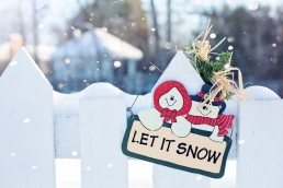 Let it snow sign on a fence