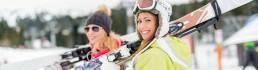 2 girls holding their skis
