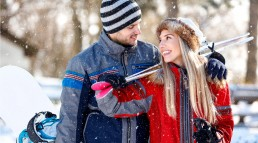 couple in the snow with skis and snowboard